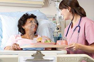 nurse-serving-senior-female-patient-meal-hospital-bed-28851147